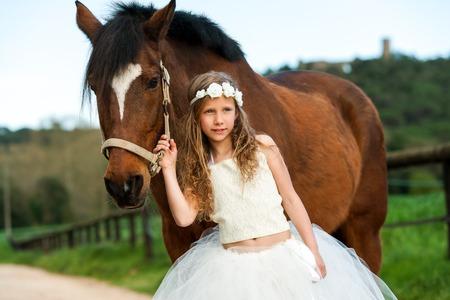 cintillos: Retrato de niña linda con la corona de flores de pie junto al caballo al aire libre. Foto de archivo