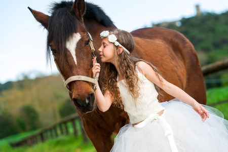 Sweet girl in white dress and flower headband whispering to horse outdoors. photo