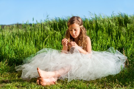 young girl barefoot: Young girl wearing white dress relaxing in green meadow. Stock Photo