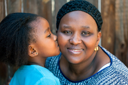 african american mother and daughter: Close up portrait of little girl kissing mother on cheek outdoors.