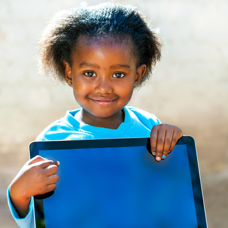 pre schooler: Close up portrait of little African girl pointing with finger at blank computer screen.