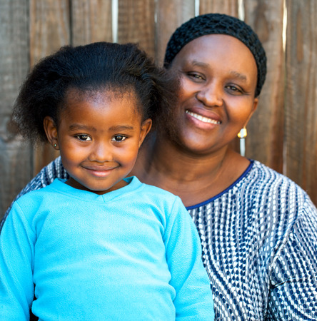Portrait of african mom and daughter against wooden fence. photo
