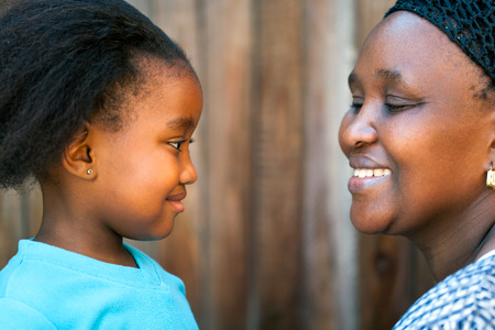 african american infant: Close up portrait of African mother and daughter looking at each other.