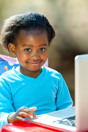 Portrait of African student navigating on laptop.
