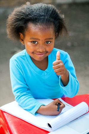 pre schooler: Portrait of little African girl doing thumbs up symbol at desk.