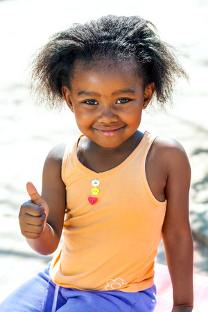 native american baby: Outdoor portrait of cute African girl doing thumbs up sign.