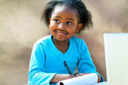 pre schooler: Portrait of African girl writing in notebook at desk.