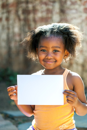 Portrait of little African girl showing blank white card outdoors.
