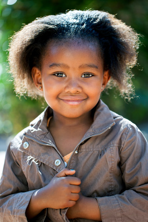native american baby: Outdoor portrait of cute African girl wearing brown jacket.