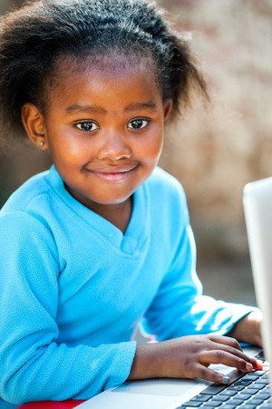 school table: Portrait of young African student learning with laptop.