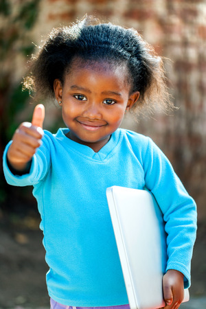 native american baby: Positive African girl with laptop under arm doing thumbs up. Stock Photo
