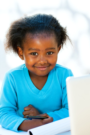 Portrait of native African kid at desk with notebook and laptop.
