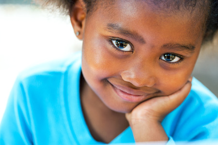 niños negros: Retrato facial de la muchacha linda de África descansando mejilla en la mano.