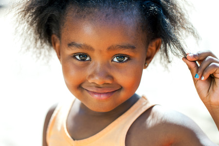 africa american: Close up face shot of cute African girl touching hair.