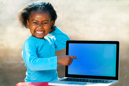 Portrait of African girl with funny face expression pointing at blank laptop screen.