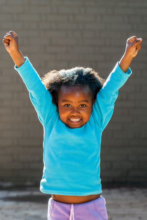 Portrait of little African girl raising arms outdoors. photo