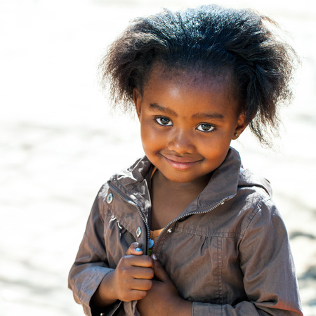native american baby: Portrait of Little African girl in brown jacket outdoors.