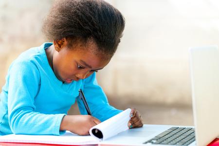 persona escribiendo: Retrato de la pequeña estudiante africano lindo haciendo las tareas escolares al aire libre.
