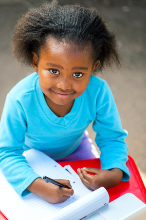 Portrait of small African kid writing in notebook at desk.