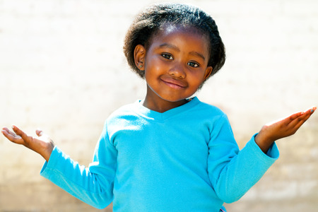 Portrait of cute African kid with arms open and wondering face expression. photo