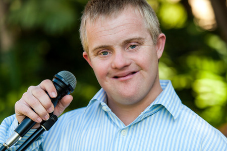 Close up portrait of handicapped boy holding microphone outdoors Stock Photo