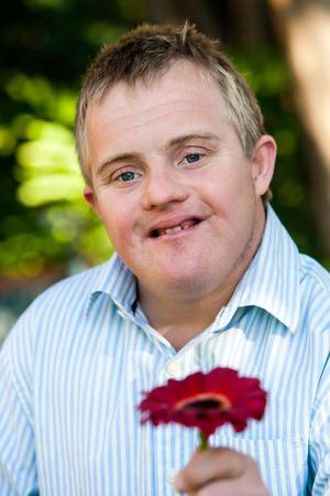 niños discapacitados: Cerrar un retrato al aire libre de un niño guapo con síndrome de down que sostiene la flor roja.