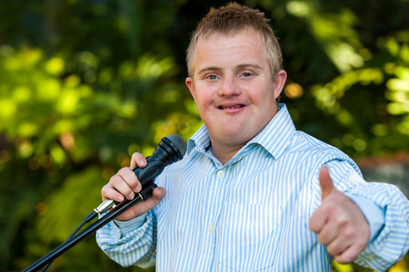 Portrait of cute Handicapped boy with microphone doing thumbs up.