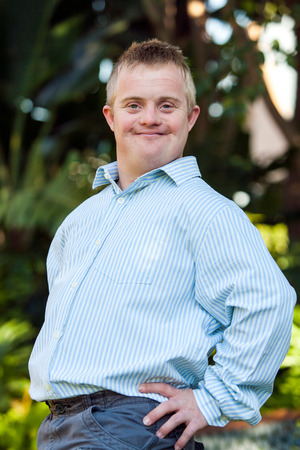 Portrait of cute boy with down syndrome posing at camera outdoors. Stock Photo