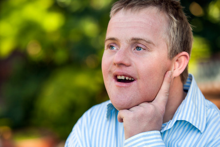 Close up outdoor portrait of cute handicapped boy looking aside with wondering face expression. photo