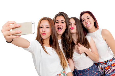 Group portrait of cute teen girlfriends taking self portrait.Isolated on white background. photo