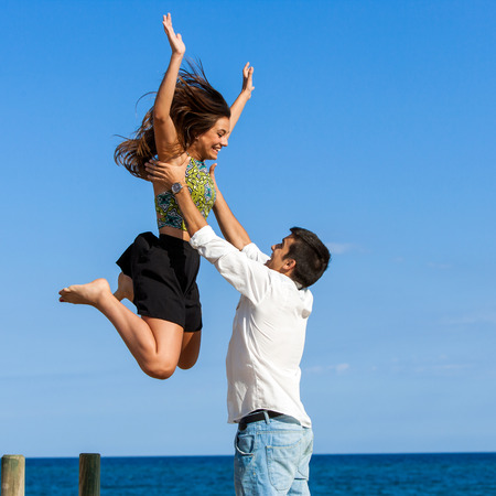 Action portrait of Girl jumping into boys arms at sea side. photo