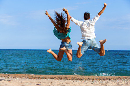 Rear view of Teen couple jumping and raising arms on beach.