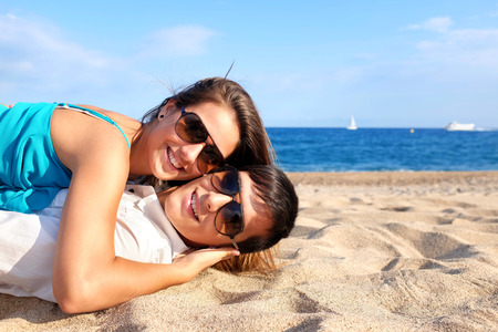 Portrait of teen Couple laying together on beach. photo