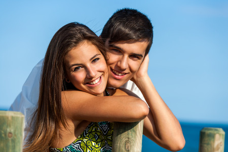 Close up portrait of handsome teen couple at sea side. photo