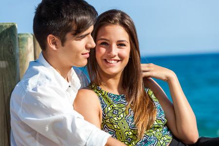 Portrait of Cute girl sitting next to boyfriend at sea side. photo