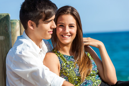 teen couple: Portrait of Cute girl sitting next to boyfriend at sea side. Stock Photo