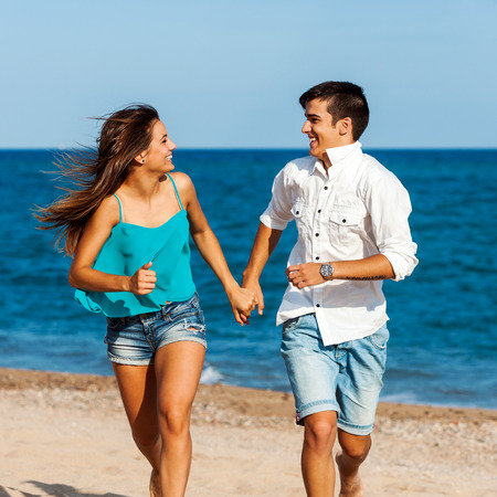 lovers holding hands: Close up action portrait of Handsome teen couple running together on beach. Stock Photo