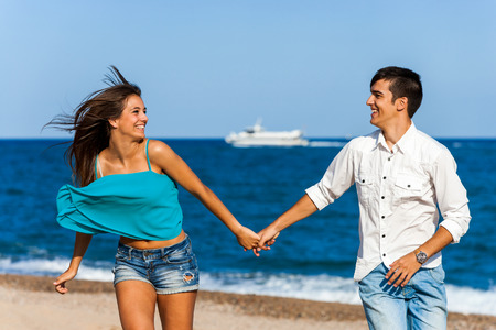 Action portrait of happy teen couple holding hands running on beach. photo