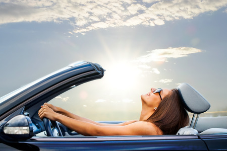 Portrait of Young girl driving cabriolet at sunset. photo