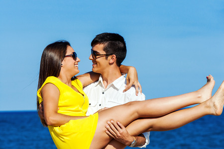 Portrait of Young man holding girlfriend in arms at sea side. photo