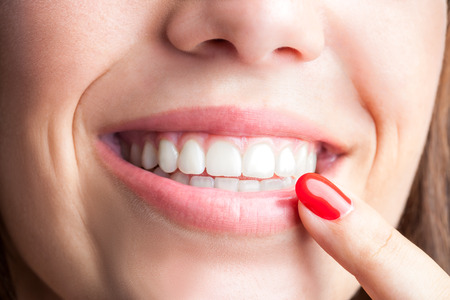 smile close up: Extreme close up of woman pointing with finger at healthy teeth. Stock Photo