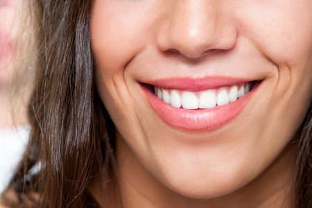 toothy smile: Macro close up of young woman smiling. Stock Photo