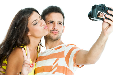 Fun portrait of cute couple taking self portrait with camera.Isolated on white background. photo