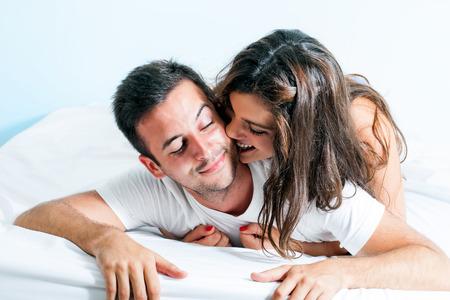 Portrét mladého páru s hravou chování v ložnici.