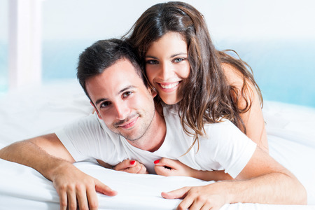 Close up portrait of handsome couple laying on bed in room. Stock Photo