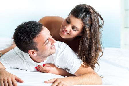 couple bed: Portrait de jeune et beau couple partage l'intimité dans la chambre. Banque d'images