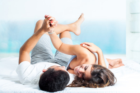 Young laughing couple laying on bed holding hands. photo