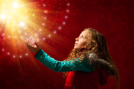 concept magical universe: Conceptual portrait of cute young girl touching the stars against reddish galaxy background. Stock Photo