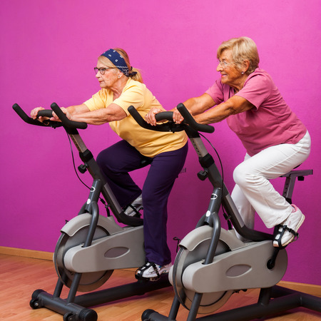 senior fitness: Portrait of two senior ladies at spinning session in health club.