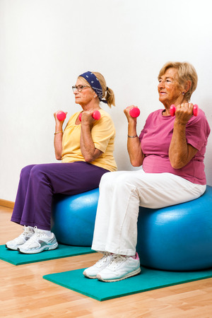 Portrait of two Senior women exercising muscles with weights in health club. photo
